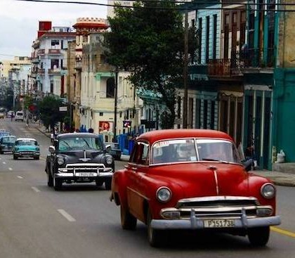 old red and blue american cars passing through Havana